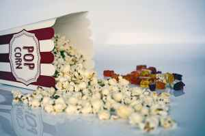 white and green pop corns beside red gummy bear
